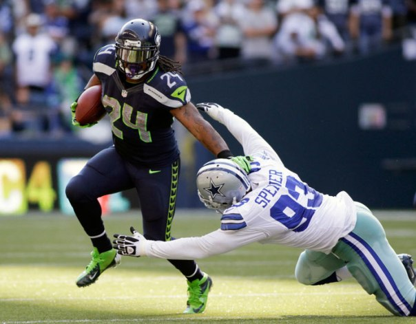 seattle-seahawks-running-back-marshawn-lynch-l-carries-the-football-as-he-attempts-to-break-free-from-dallas-cowboys-anthony-spencer-during-the-fourth-quarter-of-their-nfl-football-game-in-seattle-washington-september-16-2012